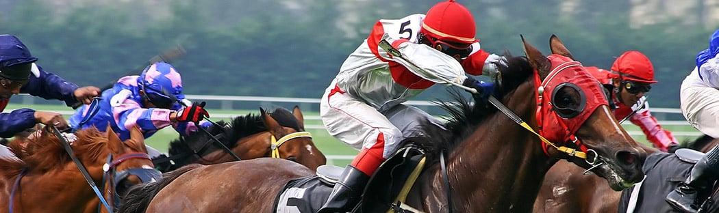 Close up of jockey atop race horse