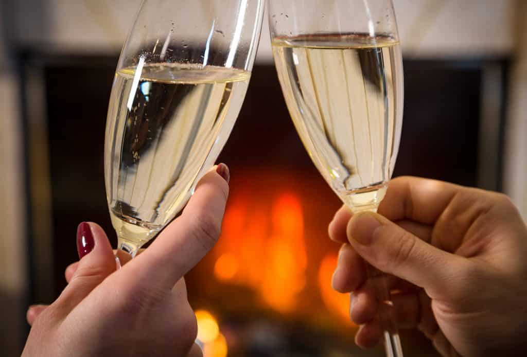 Couple clinks wine glasses fireside