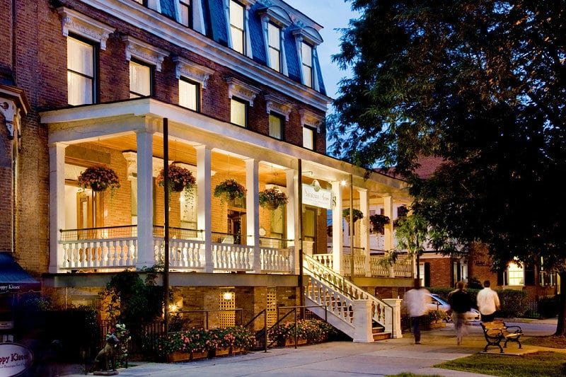 The grand porch of Saratoga Arms lit up on a summer evening, a welcoming sight in the heart of downtown Saratoga Springs