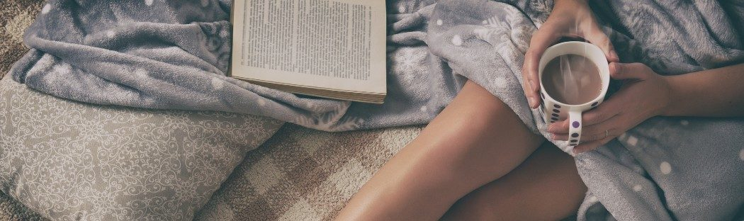 woman on bed holding hot chocolate and book